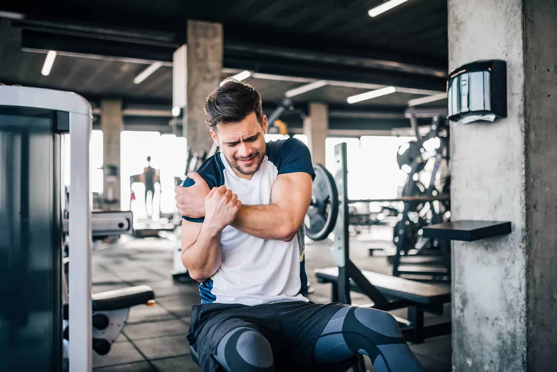 Man at gym holding shoulder in pain