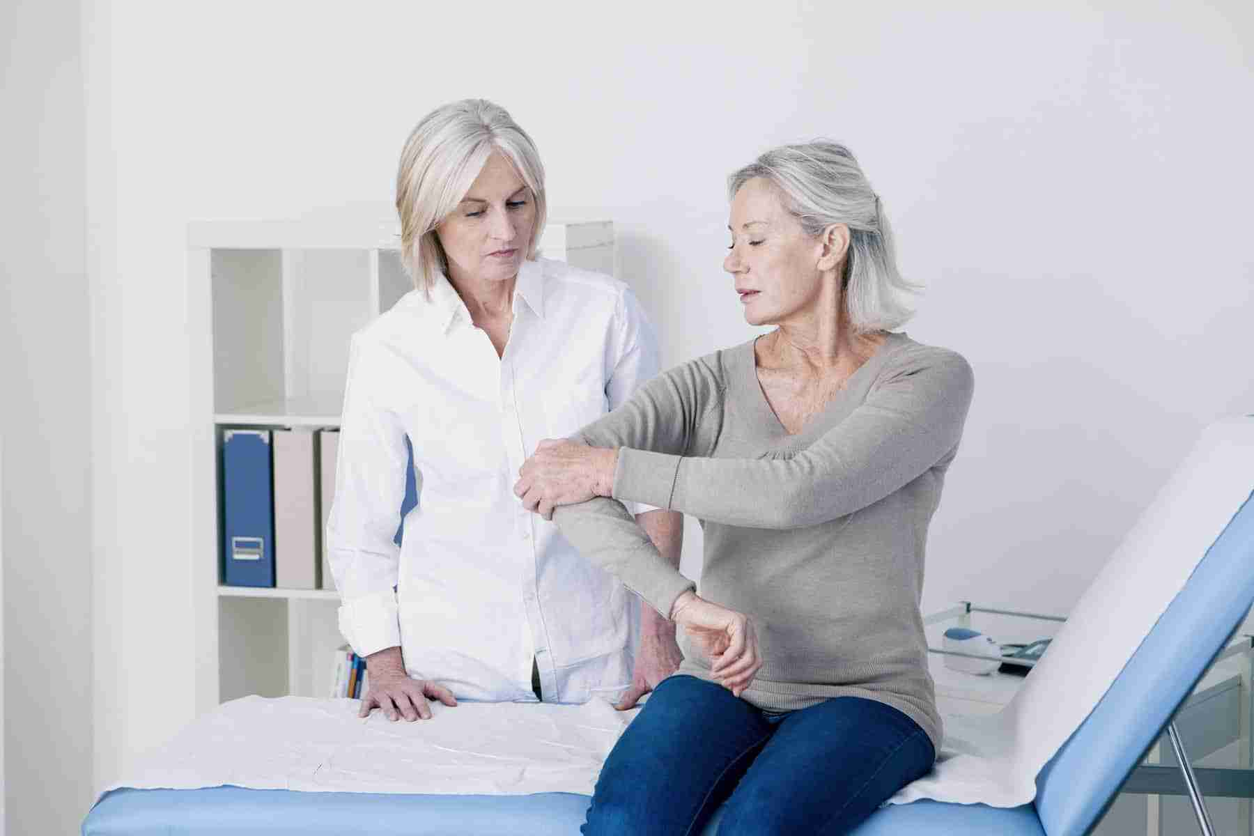 Woman testing her shoulder and elbow with doctor