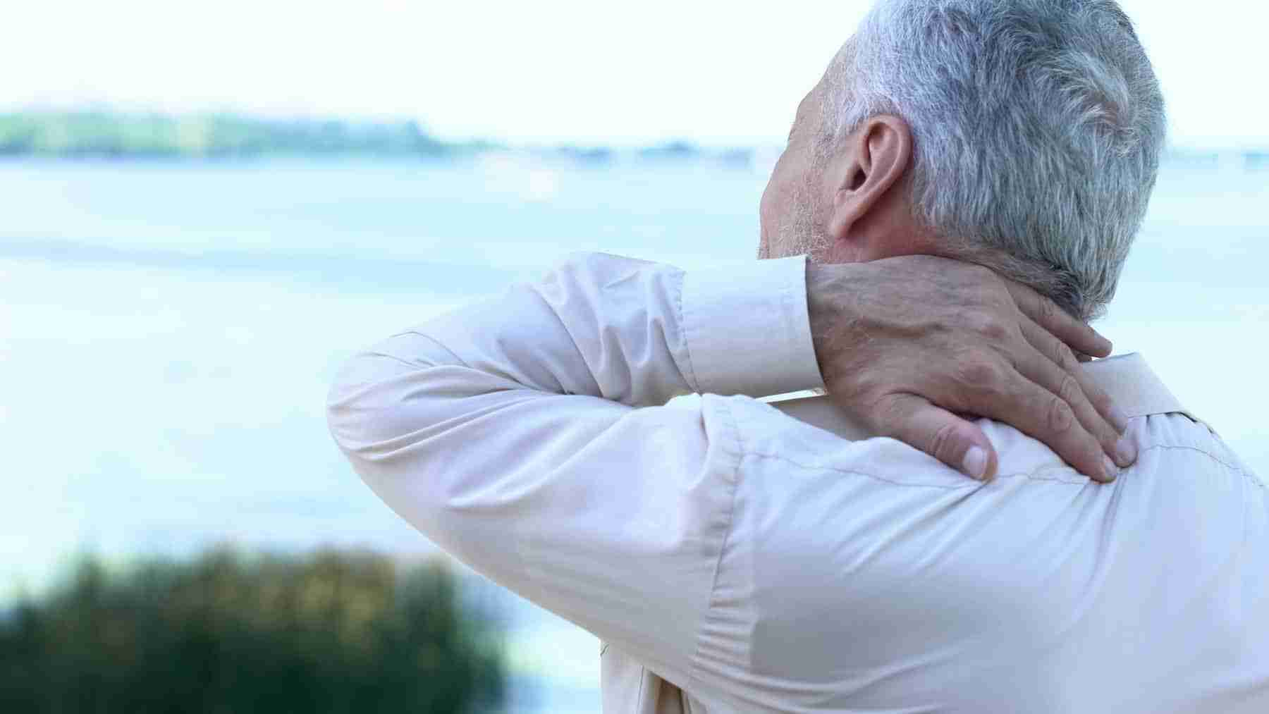 Man holding back of neck in pain